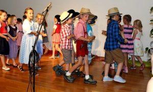 Jungen in Latzhosen Jungen tanzen in Latzhosen auf der Bühne