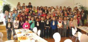 Gruppenfoto Schüler präsentieren ihre selbst gebastelten Masken und Krawatten