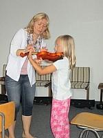 Kind mit Violine Schülerin probiert sich an einer Violine aus