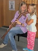 Kind mit Blasinstrument Schülerin probiert sich an einem Blasinstrument aus