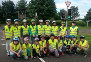 Gruppenbild Schüler mit Westen Schüler stehen auf dem Verkehrsübungsplatz mit Westen und Helmen