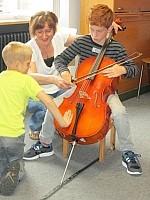 Kind mit Cello Schüler probiert sich an einem Cello aus