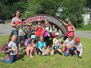"""Gruppenbild vor Bogen Schüler stehen vor einem Bogen mit der Aufschrift """"Künstler Viertel"""""""