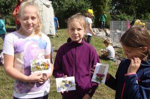 3 Schülerinnen mit einem Bild Schülerinnen zeigen ihr Naturlegebild