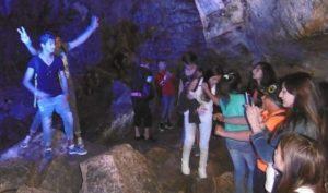 Schüler stehen in einer Höhle und machen Fotos voneinander