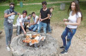 Schüler grillen Schüler stehen um ein Feuer und grillen