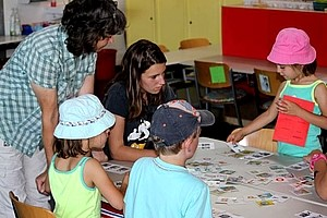 Gruppe von Kindern sitzt an einem Tisch und spielt Memory