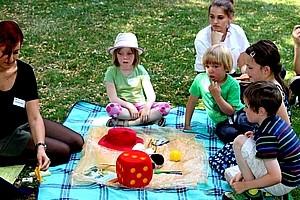 Gruppe von Kindern sitzt auf Picknickdecke und spielt mit großem Würfel