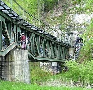 Schüler klettern an Brücke mit Helm und Gurt