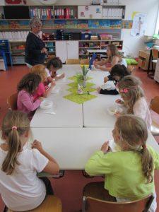 Kinder essen etwas im Klassenzimmer