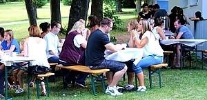 Gartenfest Gruppe sitzt auf Bänken in der Natur und unterhält sich