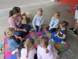 Kinder sitzen auf einer Picknickdecke. In ihrer Mitte liegt eine leere Flasche