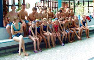 Schüler im Schwimmbad Die Klasse sitzt im Schwimmbad auf der Sitzbank