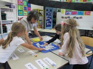 Kinder an Gruppentisch Kinder versuchen ein Wortpuzzle