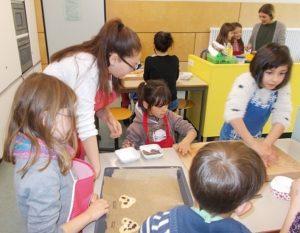Ältere Schülerin hilft und unterstützt jüngere Schüler beim Backen