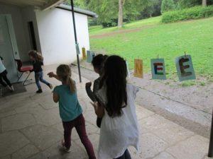 Schüler auf dem Weg in ihr Pavillon. Zwischen den Pfosten sind Blätter mit Buchstaben darauf an ein Seil gespannt