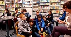Schüler lauschen einer Vorlesung aus einem Buch in einer Buchhandlung