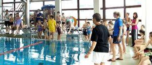 Schüler stehen um das Schwimmbecken Schülerin springt von Platte ins Wasser