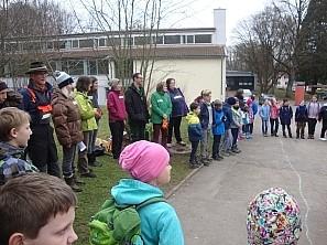 Kinder mit gefälltem Baum Schüler und Helfer stehen in einem Kreis
