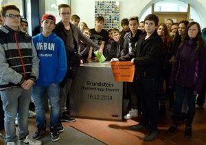 """Schüler stehen um den """"Grundstein Thyssenkrupp Elevator"""""""