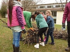Kinder mit gefälltem Baum Schüler tragen die zerschnittenen Teile des Baums
