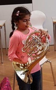 Kind mit Instrument Den Schülern werden Instrumente vorgestellt um sie für die Bläserklasse zu begeistern