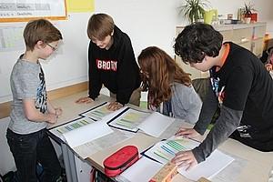 Schüler lesen Schüler schauen gemeinsam über ihre Aufgaben