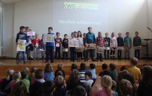 Kinder auf der Bühne Schüler heißen Schüler und Lehrer willkommen und halten Schilder hoch