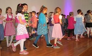 Kinder tanzen Kinder feiern ausgelassen Oktoberfest in der Schule