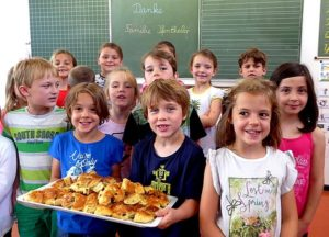 Kinder mit Gebäck Die Kinder stehen im Klassenzimmer mit Gebäck auf einem Tablet