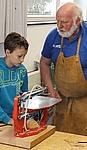 Ein Lehrer zeigt einem Schüler wie man eine Maschine bedient