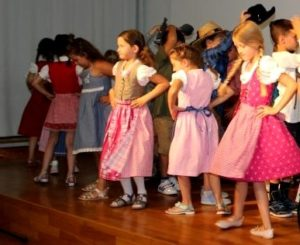 Mädchen tanzen im Dirdnl auf der Bühne
