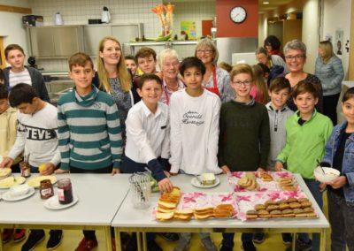 Gruppenbild Schulfrühstück Kinder und Lehrer frühstücken gemeinsam in der Mensa