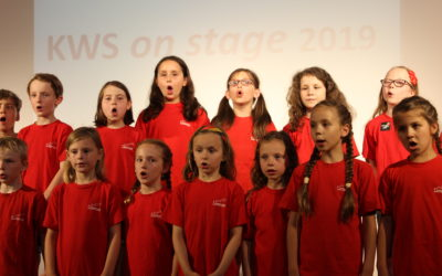 Grundschulchor singt Grundschulchor singt auf der Bühne