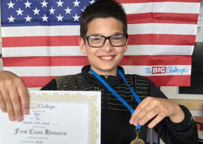 Schüler mit US Flagge und Urkunde Durch seinen Sieg erhält der Schüler eine Medaille und eine Urkunde.
