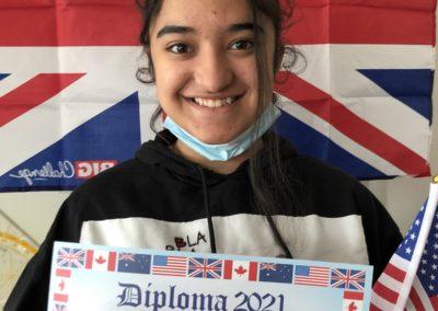 Schülerin vor Britischer Flagge mit Urkunde Durch ihren Sieg erhält die Schülerin eine Urkunde.